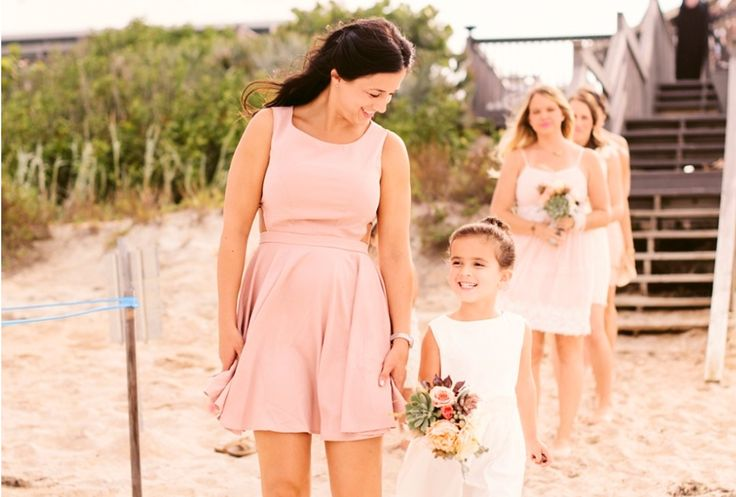 Barefoot bridesmaids walk down to the wedding site carrying  bouquets of peach and pink garden roses, cafe au lait dahlias, succulents, fountain grass dusty miller and silver brunia.