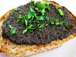 A slice of bread with olive tapenade along with a glass of wine. Perfect!