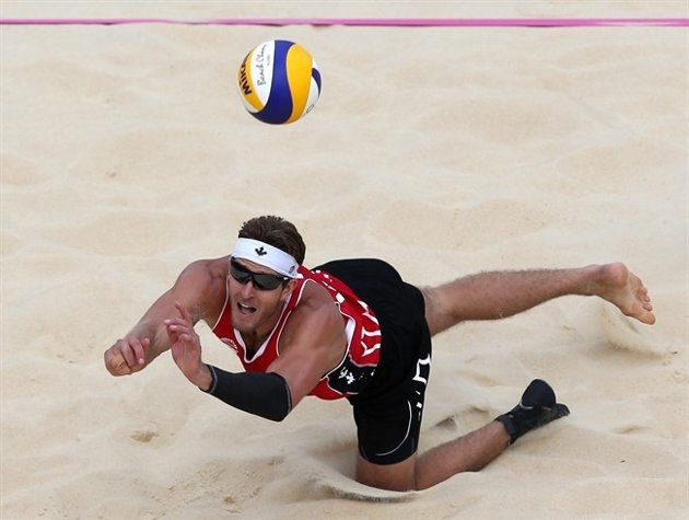 Josh Binstock from Canada reaches for a ball during the Beach Volleyball match against Great Britain at the 2012 Summer Olympics, Saturday, July 28, 2012, in London.
