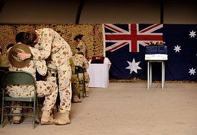 Emotional farewell: two soldiers console each other during the memorial service in Tarin Kowt. (Australian Defence Force: CPL Christopher Dickson )