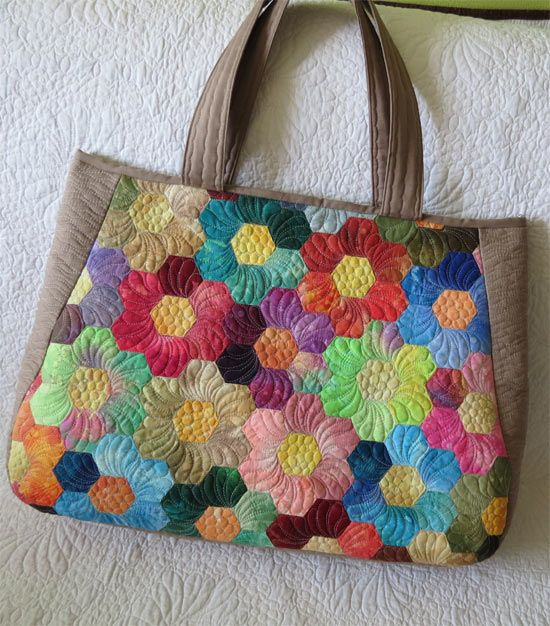 Geta's Quilting Studio: Notre Aventure Parisienne - plain hexagon piecing becomes beautiful flowers with petal quilting surrounding the center pebbling.