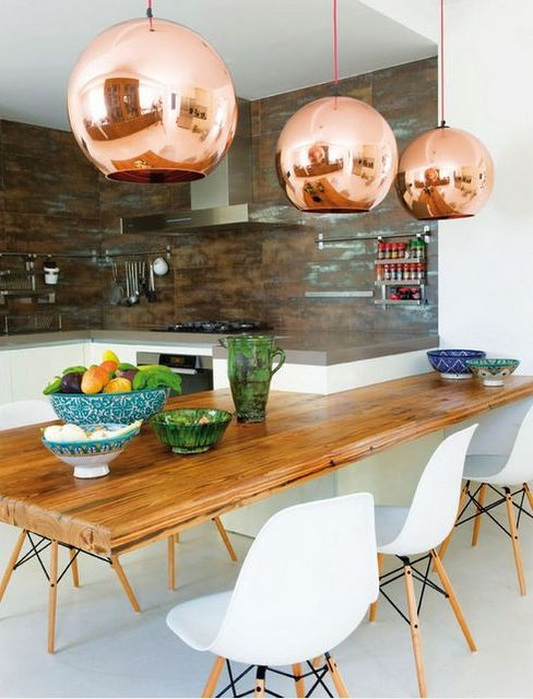 Organic modern dining rooms have a lived-in elegance that comes from balancing hard and soft elements. They are cool, calm, and collected, while inviting you to share the space with family and friends. This one's mix of blonde wood, Eames molded dining chairs, copper pendant lights and dark backsplash offer the perfect mix of modern elegance and kid-friendly living.