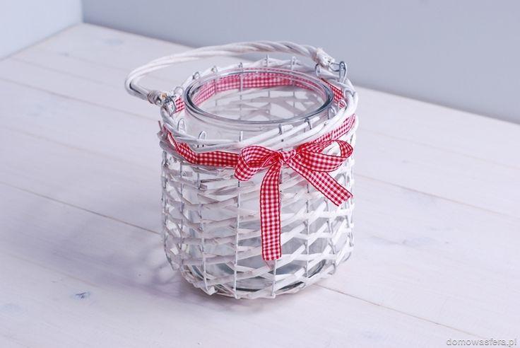 Duży lampion z wikliny o dużych oczkach. Wyjątkowa latarenka posiada szklany wkład oraz uchwyt, za pomocą którego można ją powiesić. Całość ozdobiona jest czerwoną wstążka w biała kratkę.