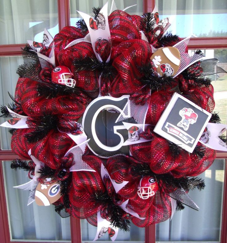 Georgia Bulldogs Fan Deco Mesh Door Wreath Fan Deco Mesh Door Wreath. This Georgia Bulldogs Fan Deco Mesh Door Wreath Fan Deco mesh wreath is made with deluxe Red Black deco mesh on a red metallic wreath,The wreath is trimmed with red and black ribbon and top off with a hand painted Texas Tech logo that's sealed for weather protection. This Crazyboutdeco mesh wreath also features 2 Licensed Riddell Texas Tech Football helmets and is top off with 2 Footballs to make it perfect for your…