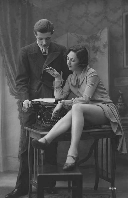 "Woman reading while striking a typewriter key, 1920s. The typewriter-girl gave rise to a new cultural fascination with gendered roles, with how well those roles became firmly and strictly adhered to, and how they became deeply conflicting and problematical. The typewriter embodies the muddying of concrete gender roles: the ""masculinity"" associated with the realm of business, financial independence, and continuous labour becomes integral to the typewriter-girl's cultural significance."