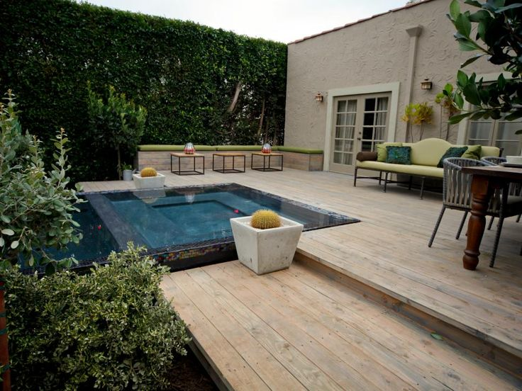 This spacious back deck features an infinity swimming pool and a contemporary lime green couch. A built-in bench with green cushions provides additional seating, while tall hedges offer privacy.