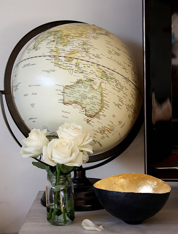 Neutral colored globe with pretty black & gold bowl and white roses