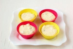 Выложить творожную массу в смазанные растительным маслом формочки для кексов (приблизительно по 2-2,5 столовых ложки в одну форму).