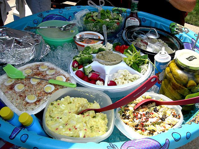 Keep Things Cool in a kiddy pool placed on a picnic table and then everyone is able to put their foods right on the ice when they arrive