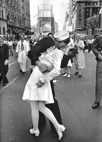 """The Victory Kiss; this famous photo taken by Alfred Eisenstaedt In Times Square after President Truman announced the end of World War II on Nov.14,1945. This Iconic photo captured the spontaneous kiss of an American Sailor and a young woman in white, it became famous when Life magazine put it on the cover of their """"Victory"""" addition the following week."""