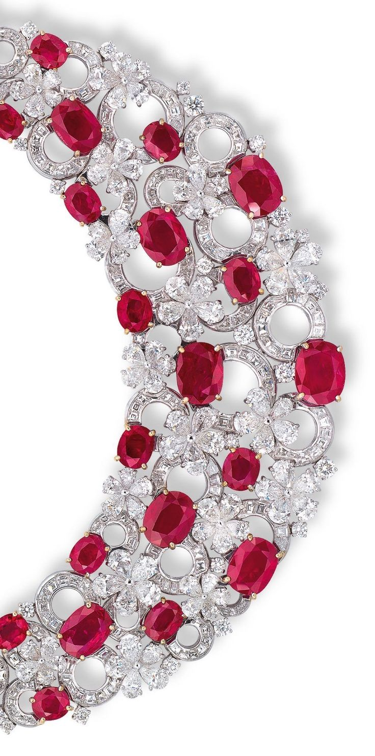 AN IMPORTANT RUBY AND DIAMOND 'FLORA' NECKLACE, BY BULGARI. The bib necklace, designed as an openwork panel of thirty oval-shaped rubies weighing from 7.00 to 1.21 carats, connected by keystone and whistle-cut diamond overlapping circular links, interspersed by pear-shaped diamond florets, accented by brilliant-cut diamonds, extending to the backchain, mounted in 18k white and yellow gold, 36.0 cm long, in black leather Bulgari case. Signed Bulgari. #rubynecklace #diamondnecklace