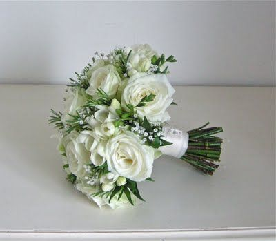 wedding bouquet in whites and greens using avalanche roses, freesias, gypsophila, a touch of fine foliage and diamante sprays to compliment the detail on her wedding gown.