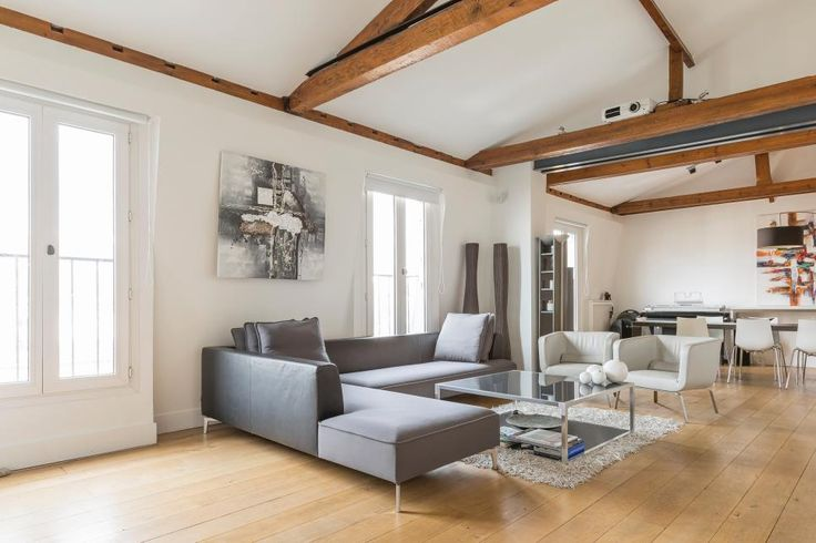 Light wood floors ground this urban living room, which features a gray contemporary sectional, a glass coffee table and exposed ceiling beams.