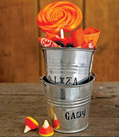 Personalize galvanized buckets with adhesive or rub-on letters for a Halloween table. Fill with treats for guests to take home at the end of the party.   - CountryLiving.com