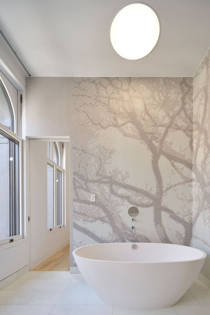 Architectural design firm WORKac, have completed the renovation of a historical building with a cast-iron facade in New York City, and transformed it into modern apartments. This renovated bathroom has a standalone tub surrounded by tile mural.