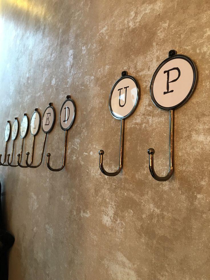 Typewriter styled coat hooks spell 'DOLLED UP'
