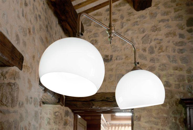 Farmacia è una serie di lampade a sospensione ad una, due o tre luci, regolabili in altezza al momento dell'installazione, con asta in ottone anticato, rosone in ceramica bianca e diffusore in vetro bianco latte lucido.