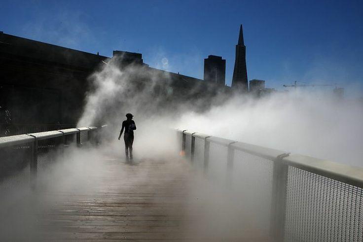 "A pedestrian walks across ""Fog Bridge"", a 150 foot long bridge next to the Exploratorium by artist Fujiko Nakaya in San Francisco."