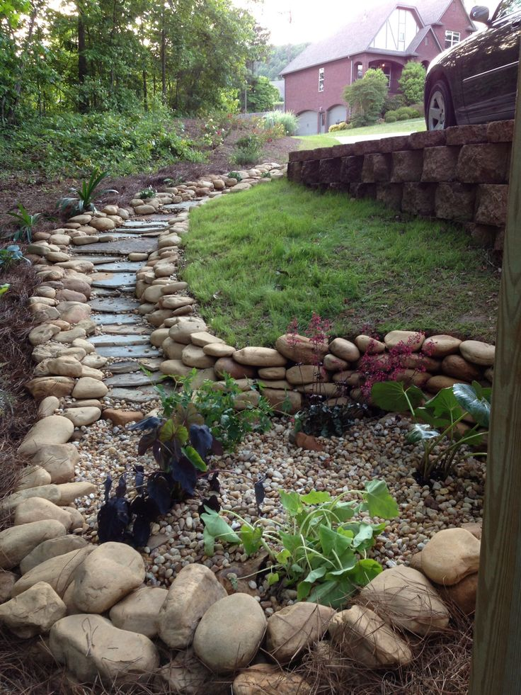 The dry creek bed that ends into a rain garden. I designed and built it on my own. Used flagstone and slate to make the middle and small river rock to fill in the gaps.