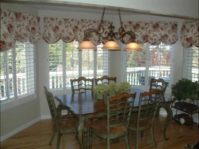 Plantation shutters with a fabric valance in a dining room for Shutter window treatment ideas