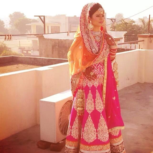 Stunning Indian bride at sunset. Her fuchsia, orange and gold lehenga absolutely radiates in this photograph.