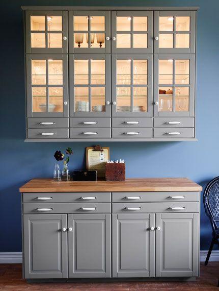 Módulo montado na parede com portas de vidro, iluminação de armário e gavetas altas, combinado com uma módulo independente com gavetas, portas e bancada em madeira maciça