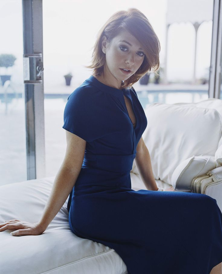 Alyson Hannigan. Sitting on... something white and comfortable-looking. This picture is both adorable and sexy. It is distracting me from whatever kind of furniture that is.