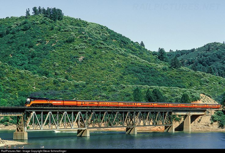 The beautiful Worlds Fair Daylight headed by 4449 Southern Pacific Railroad GS-4 as it  crosses over Lake Shasta, Lakehead, California with swimmers below waving to the fireman.