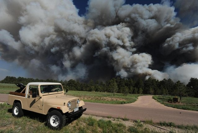 Bill Moreau watches as the Black Forest fire burns near his house near Black Forest Road Tuesday afternoon, June 11, 2013, near Colorado Springs, Colo. The Black Forest Fire was one of at least three significant wildfires burning in Colorado amid gusty winds and record-breaking hot, dry weather. (Photo by Christian Murdock/AP Photo/The Colorado Springs Gazette) http://avaxnews.me/fact/Colorado_Fires_Growing.html