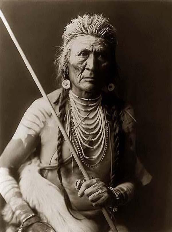 You are viewing an unusual image of an Indian Brave Holding His Spear. It was taken in 1908 by Edward S. Curtis.    The image shows a Crow (Apsaroke) man holding a Spear. He is wearing a shell necklaces and War Paint.    We have created this collection of images primarily to serve as an easy to access educational tool. Contact curator@old-picture.com.