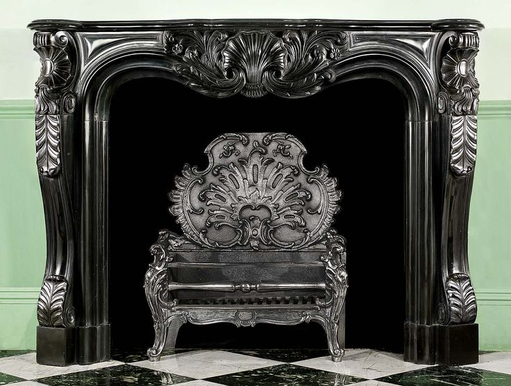 Antique French black marble Louis XV rococo fireplace mantel.