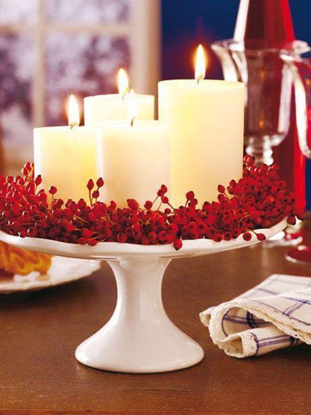 Una base de torta de cerámica blanca, adornos de flores tipo frutos rojos y sobre este arreglo 4 velas blancas de distinto tamaño.
