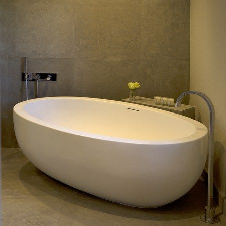 A luxurious bath with a beautiful floor-mounted filler and bespoke controls creates a relaxing corner in this Cotswold cottage.⠀