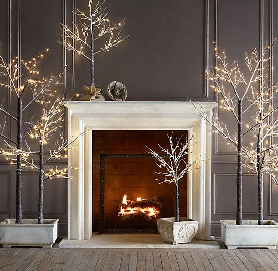 Dramatic modern holiday decor with tree lights against dark wall. Get the look with Dunn-Edwards Paints Charcoal Smudge DE6370 for your wall color and Milk Glass DEW358 as your trim color.