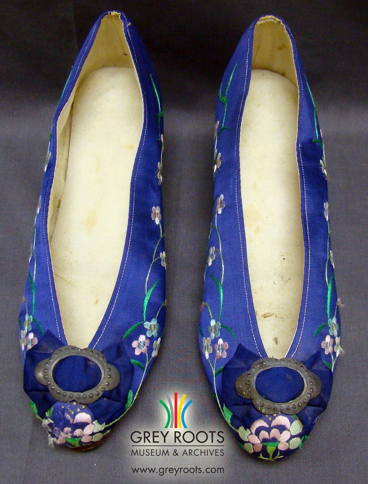"""A pair of floral-embroidered, bright-blue, ladies' pumps which were imported from Hong Kong. The exterior of the pumps is made of silk and is embroidered with pink, white, blue, and green silk floss threads while the inside is lined with a once-white cotton fabric. The maker's mark is a bell-shaped logo accompanied by an English address for a shoe maker from """"No. 171 Hollywood Road, Hong Kong"""". Grey Roots Museum & Archives Collection."""