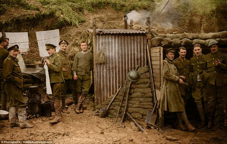 A group of soldiers hang up clothes as they relax outside a shelter near the trenches of t...