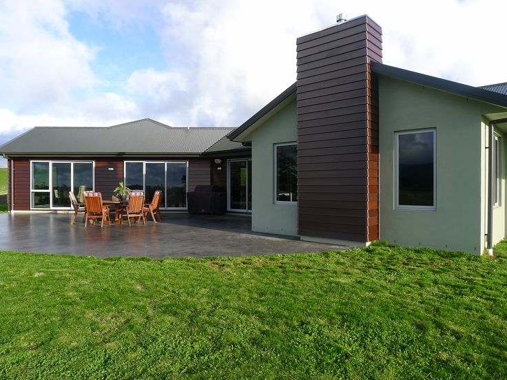 A smooth concrete arc creates an easy outdoor environment for this weatherboard and plaster home.