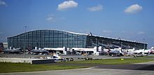 Planes congregate by a building. London Heathrow Airport, England.
