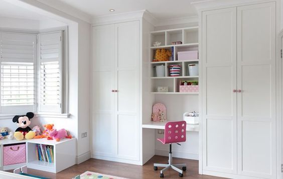 Floor to ceiling fitted wardrobes with desk area in white satin lacquer.: