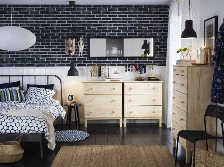 A medium sized bedroom furnished with a gray metal bed for two combined with chest of drawers in unfinished solid pine.