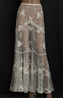 1905 lace/tulle under skirt, Made from cream colored cotton tulle, the skirt is appliquéd with large tape lace bows, small princess lace flowers, and Irish crochet rosettes. It is longer and fuller in back, forming a small train.
