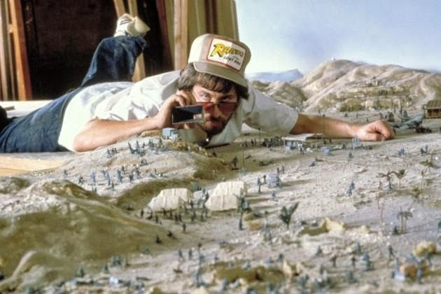 Steven Spielberg taking photos of some of the set pieces that were made as miniatures for the first Indiana Jones movie Raiders of the Lost Ark.