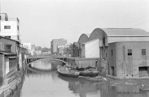 昭和毎日:池田信『1960年代の東京』 神田川。日本橋川との分流点。小石川橋から後楽橋を見る。川の右側は千代田区。左側は文京区。右手は収集したゴミを処理施設に運ぶために設置された船舶中継所。神田川は飯田橋付近から中央線に沿って、水道橋駅・御茶ノ水駅の北側を流れ、浅草橋駅の東で隅田川と合流する。神田川の前身は平川と呼ばれ、中世までは飯田橋から一ツ橋を経て、大手町付近から日比谷入江と呼ばれた海に注いでいた。江戸時代の1620年、神田山・神田台を開削する大規模工事を行い、それまでの流路を東向きに変えたのが神田川で、またその土砂で日比谷入江を埋立て市街地を造成した。小石川橋付近から九段堀留までの平川の旧水路は埋立てられたが、1900年になって現在のような流路に復活され、外濠川と呼ばれた。日本橋川と改称されたのは東京オリンピックのあった1964年になってから=東京都千代田区神田三崎町2丁目(後の三崎町3丁目)付近で 1962年(昭和37年)6月1日、池田信(いけだあきら)さん撮影 毎日新聞社刊「1960年代の東京」158―159ページ掲載