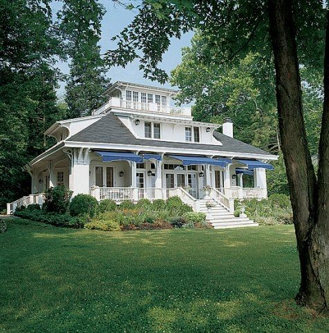 1916 house on the shores of the Potomac with blue awnings, widow's walk, covered porch. Photograph by Gordon Beall, from Architectural Digest