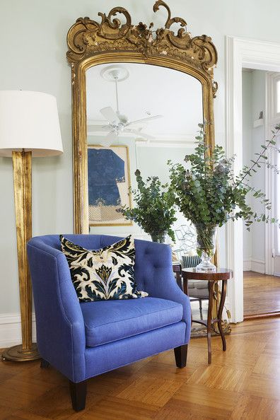 A metallic floor lamp and gold-leaf mirror paired with a violet tufted chair in the living room of Villa Sophia, designed by Juan Carretero.