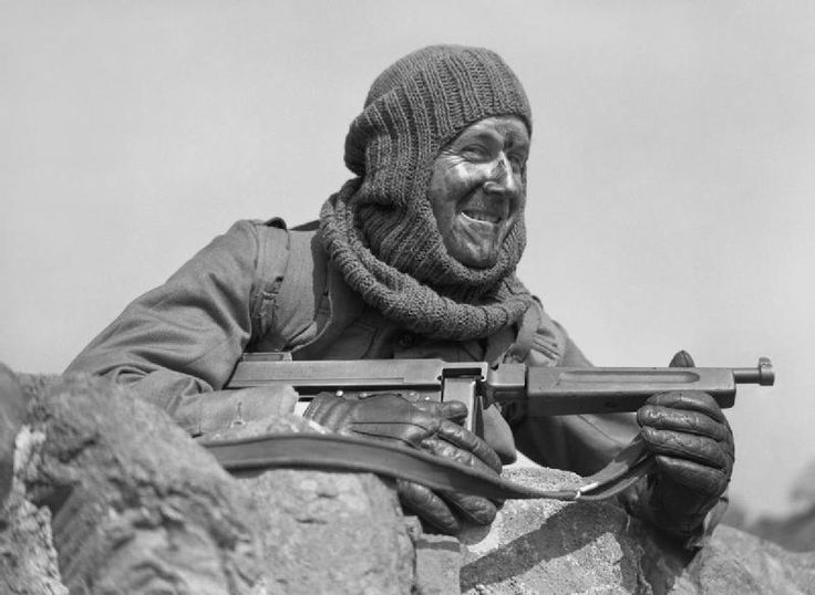 Portrait of a soldier from No. 3 Commando armed with a 'Tommy gun' and wearing a balaclava, at Largs in Scotland, 2 May 1942 .   By 1942 Britain's 'Special Forces', mainly the Commandos, were beginning to become established and were mounting an increasing number of raids on occupied Europe and behind enemy lines in the desert. Some raids were spectacular successes such as at St Nazaire, whilst others such as Dieppe are now largely viewed as disasters.