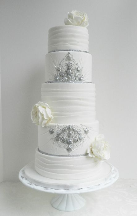 White wedding cake with silver accents.