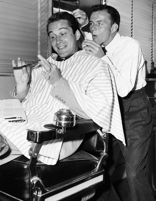 Frank Sinatra gives Perry Como a trim at the barber shop on the MGM lot, 1948