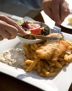 """Fish and Chips (peixe e fritas) Peixe frito empanado (geralmente bacalhau fresco) com batata frita cortada grossa. O preço varia de 6 euros em um """"take-away"""" até 20 euros em um restaurante."""