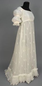 1799-1810   Gown Side View.                       Cotton and embroidered muslin, probably Bengali, all-over sprigged Broderie Anglaise, short sleeve with three pairs of inside ties to adjust double puff, ruffled edge, back tie at neckline and high waist, ruched band above slightly trained hem with scalloped sawtooth border, cotton bodice lining.        whitakerauction.smugmug.com      suzilove.com